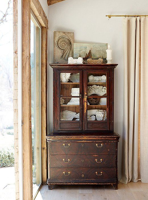"""An antique Italian cabinet with embossed leather interior adds storage and is a display place for ornamental plaster pieces. """"Like in Steve's office, we used large single-pane glass to provide great views of the pond and the donkeys,"""" says Brooke."""
