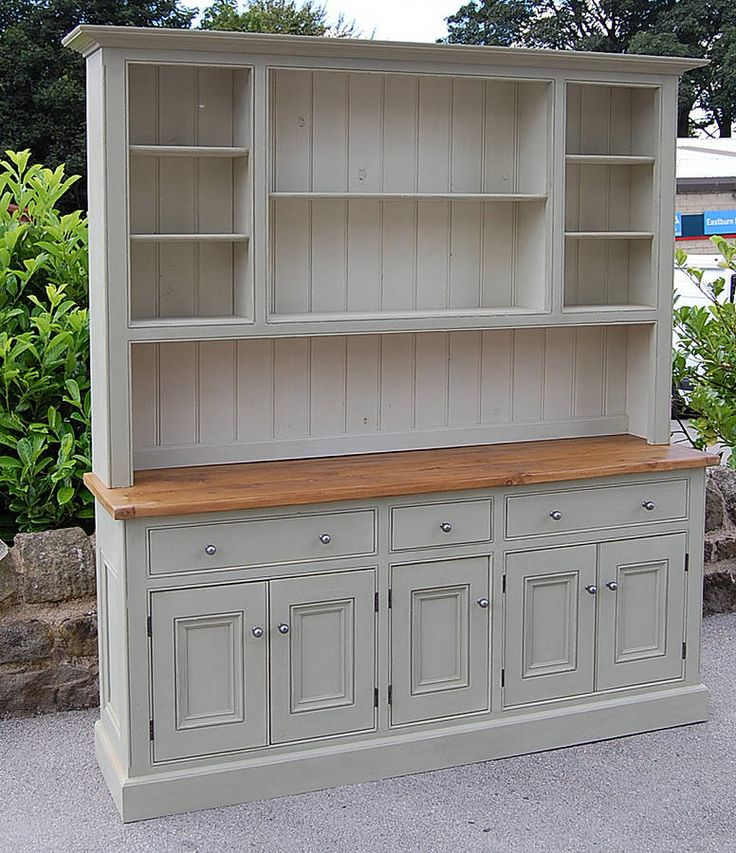 This painted solid timber dresser has metal canon ball handles and a reclaimed wood top.This dresser is handmade in our workshop from reclaimed solid timber, with an oiled oak worktop. The top of the dresser has open compartments for displaying kitchen items, while the base houses two double cupboards and one single cupboard, with three matching drawers above. This dresser is made to order and can be painted from a selection of Farrow & Ball Colours. Please select from the drop down m...