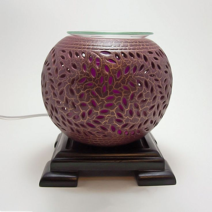 Ceramic Clay Round Electric Scented Oil Fragrance Warmer - OWEO501 - Round electric scented oil fragrance warmer with swirl cutouts that allow the light to shine thru. Deep purple with gold accents. Smooth tinted glass bowl for your fragrance choice. Wood base. Built -in oversized cylinder protects the halogen bulb.  Dimmer dial, with on / off switch,  lets you control the light, heat and aroma intensity. FOR SALE