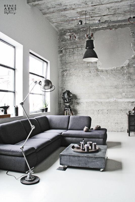 コンクリート打ちっぱなしのような空間に、グレーのカウチソファ。 シンプルな家具でも、照明をメタリックな素材にするだけでインダストリアル。
