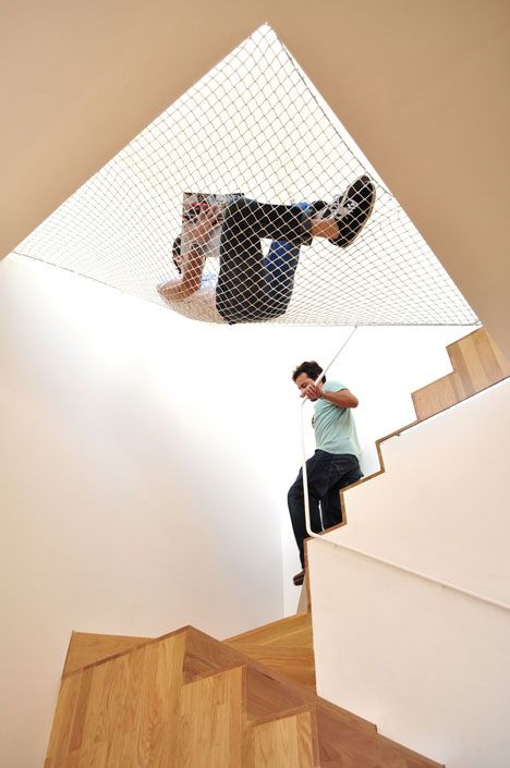 """""""A suspended net provides a hammock over the staircase of this apartment in Porto by architects OODA."""""""