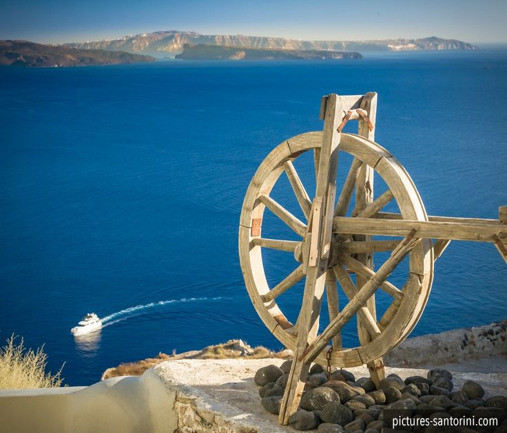 Wooden wheel in front of the caldera of the island of Santorini.