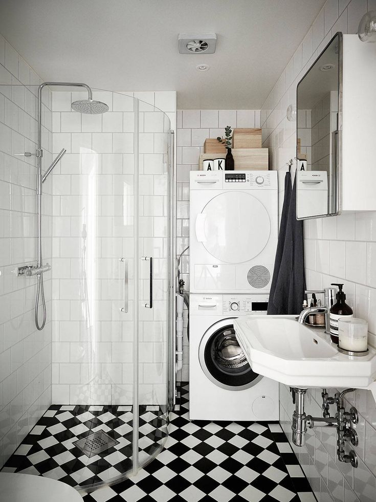 Compact laundry: washer stacked on dryer in corner of bathroom, black and white chequerboard floor, white square tiles in subway pattern with light grey grout, wall-mounted basin with chrome bottle trap, chrome tapware, mirror cabinet