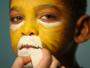 To create a base for your lion makeup, begin by dampening a sponge then picking up some of the yellow face paint. Tip: When using dry face paints, be sure to get sponge or brush wet before dipping into paint. Have child close their eyes, then apply yellow paint to the center of their face and blend out. Using the same sponge, add orange to the yellow paint's edges and blend out further to create a blended ombre effect. Apply orange paint like brushstrokes to resemble fur. Dip a clean sponge…
