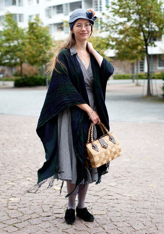 """My godmother gave me the shoes when I was 16 years old. At that time these cloaks were in fashion, too. The hat I bought at handicrafts fair in Bonn, the dress is from Lindex and the 60's bag is a souvenir from Madeira.I like black, brown, grey and green. I never wear bright colours. I like second hand, dresses, skirts and simple clothes. A hat is a must."""