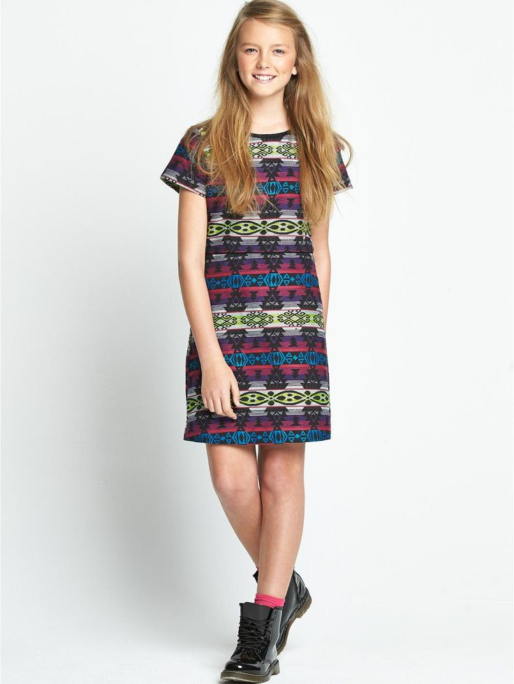 Freespirit Girls Jacquard Dress with Bright Aztec PatternsGet her ahead of the fashion pack with this girls trendy tribal printed dress by Freespirit.In a textured fabric, the bright Aztec patterns and ethnic stitching lend a fun boho feel to her look. The structured style features panels to the top and waist making this dress a great choice for parties and special occasions, while the jazzy prints are injected with flashes of vibrant neon colours for a quirky-cool finish.She can wear this…