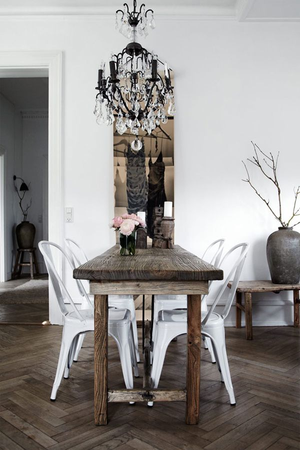 A vintage chandelier, furniture made of reclaimed wood and modern Tolix chairs in the dining room