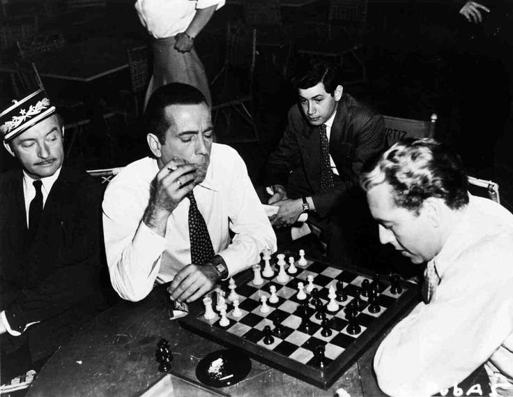 Claude Rains watching Humphrey Bogart and Paul Henreid play a game of chess on the set of Casablanca | Rare and beautiful celebrity photos