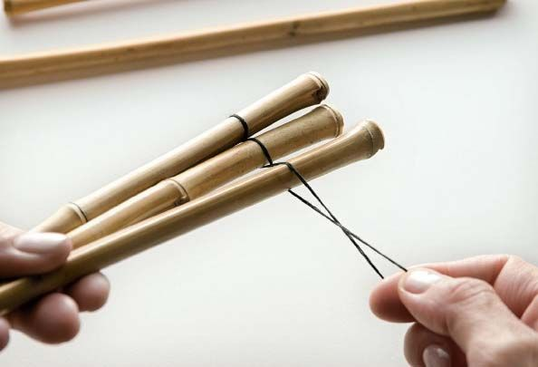 A cerca de 5 cm de cada extremidade da saboneteira, passe o cordão em volta das varetas de forma cruzada, pois assim o bambu não se soltará. Dê três voltas, para ficar bem firme, e finalize com um nó.