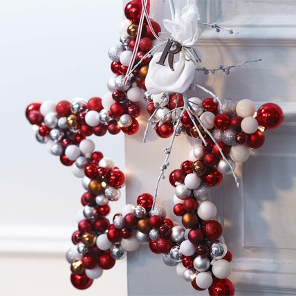 Star wreath of Christmas baubles  -- and garland of shiny baubles with glitter decorated in red, silver and copper. 20 battery-powered LED lights illuminate the wreath in a star shape, which is also suitable for outdoor fine.