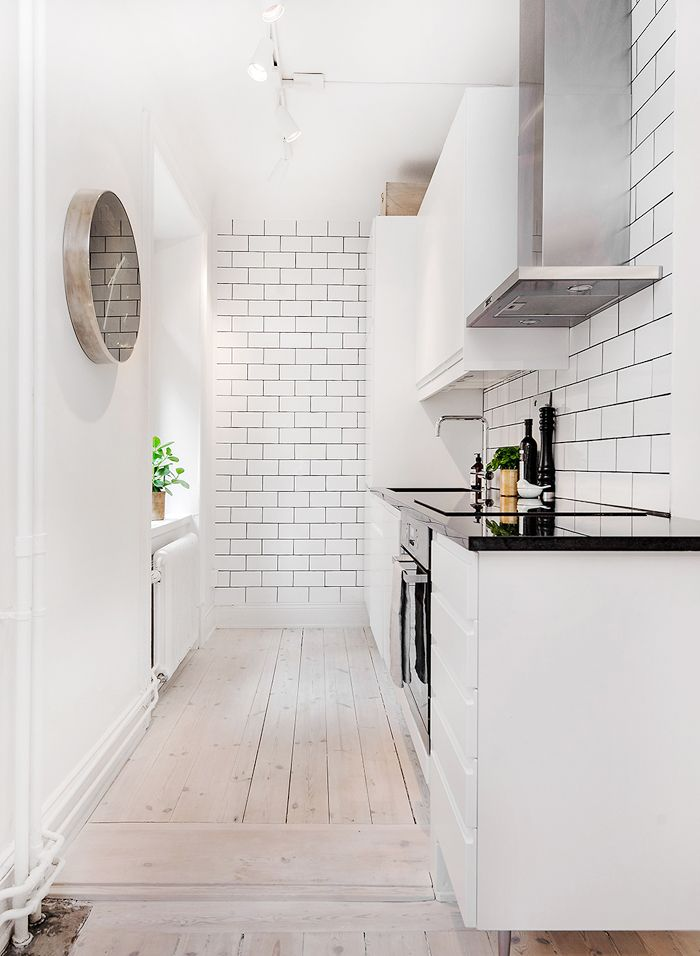 I would love to have my kitchen as clean as this one. Love the white brick walls together with the wooden floors.