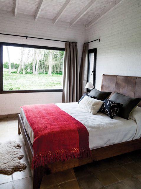 La suite de esta casa de campo tiene una cama matrimonial con acolchado en color crudo, manta bermellón, almohadones en gris y negro, y respaldo en marrón.