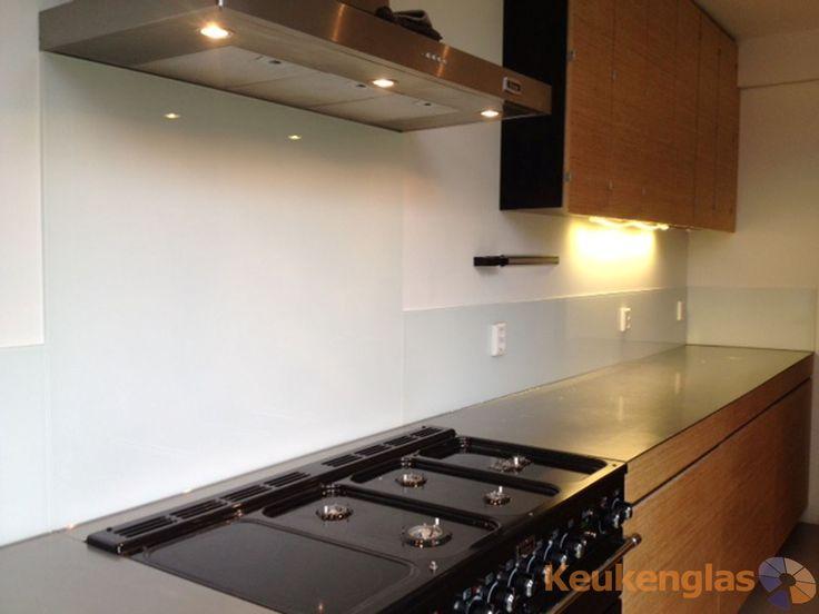 Deze houten keuken in Haarlem hebben wij voorzien van een witte glaswand op de keukenmuur.