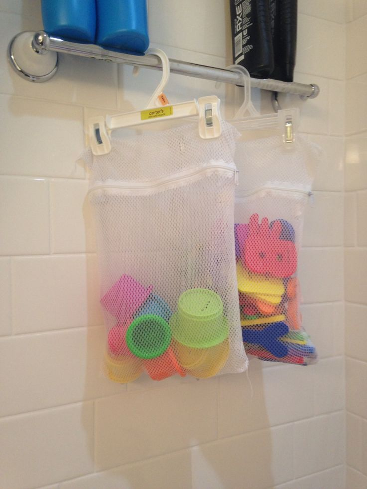 Bath toy storage hack. Cheap mesh lingerie bags and baby size pants hangers. Bath toys are put up and able to dry. No more mold or mildew growing on the toys and they're out of the way for mom or dad's shower. I got these bags from the $1 section at Target some time ago.