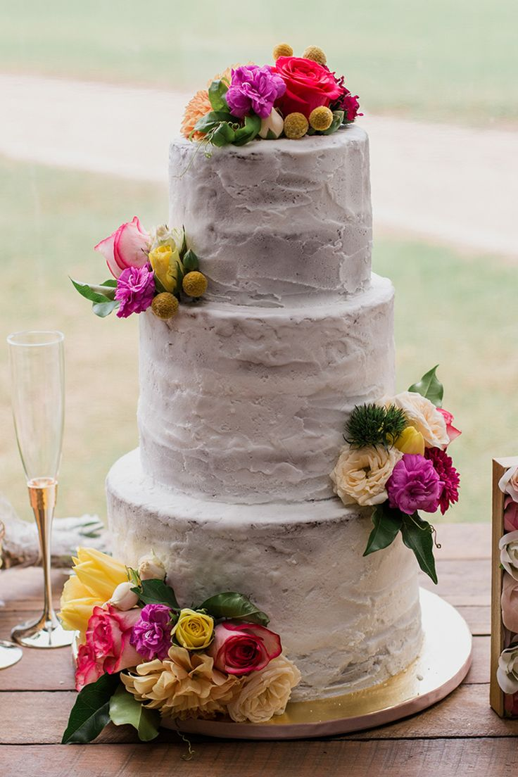 Bright garden wedding cake with pink and yellow flowers | Bless Photography | See more: http://theweddingplaybook.com/joyful-and-bright-garden-wedding/