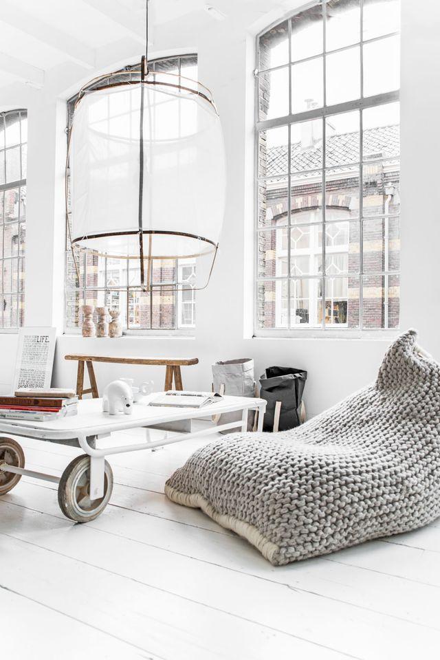 Salon d'une blancheur éclatante avec un fauteuil douillet en coton