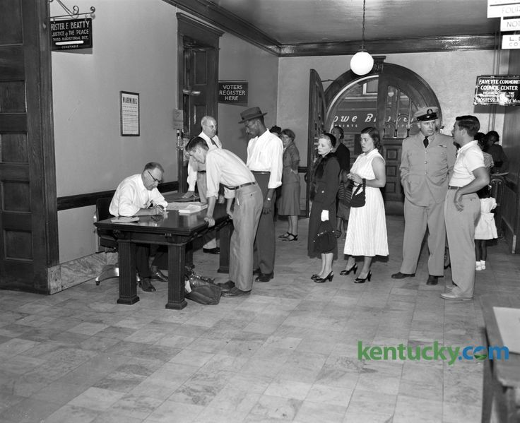 Because of the great number of Fayette countians registering to vote in the November election, the county clerk's office placed an extra desk in the hall outside the registration office on September 5, 1952 to take care of the overflow. At left, Robert Ledford, deputy clerk, registered Bill DeRossitt while others waited in line in the Fayette County Courthouse hallway. The voter registration office was to close on September 6 until after the election, which took place November 4. A total of…