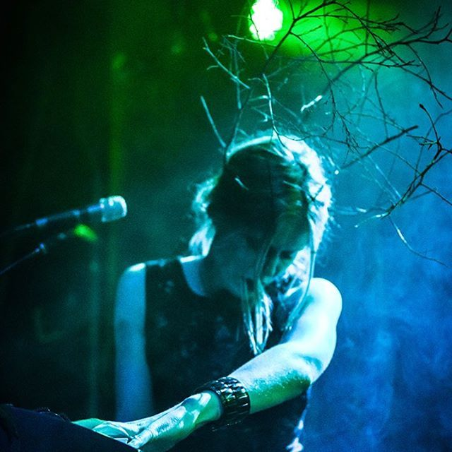 """""""As the angel gave way to the beast inside, she snapped the twigs off her head and threw them into the stunned sea of faces in front of her. A twisted tree branch served up the two microphones needed for her split personality; one for the foreign songs of sadness, and the other to exorcise the demon within. Review by http://ilistensoyoudonthaveto.com photo: Mattie Jensen"""