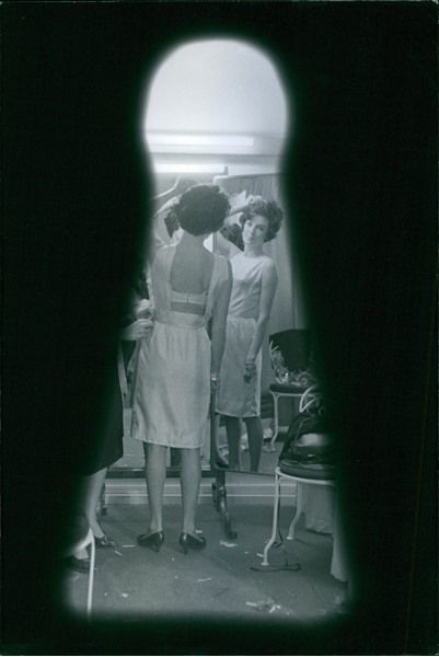 Vintage photo of Female model trying a new dress.  -