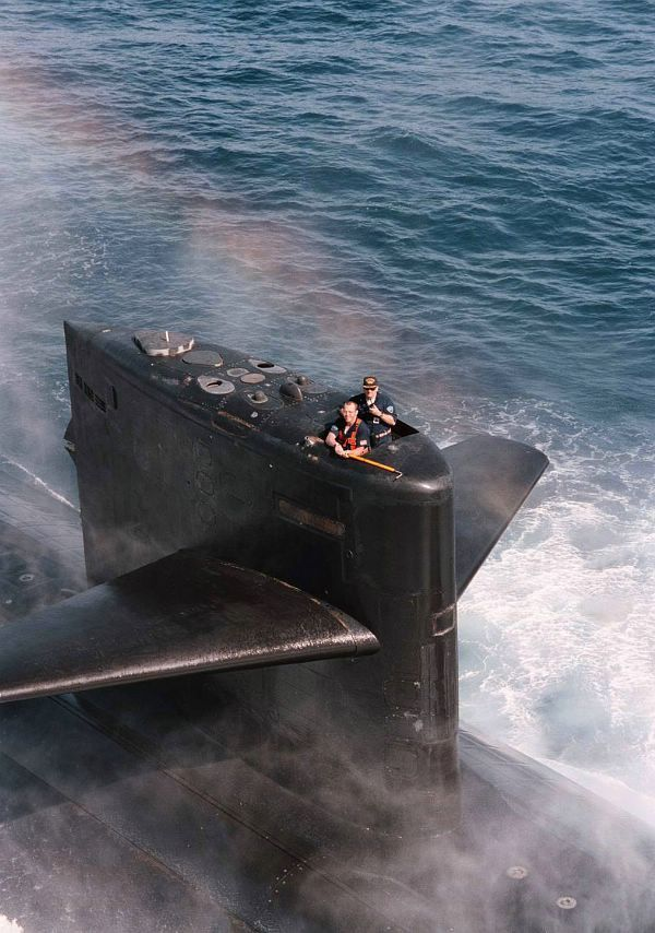 Crewman on board the U.S. Navys Los Angeles-class attack submarine USS Baltimore (SSN 704) stand by with a grappling hook to snag a mail shipment being lowered by an SH-60 Seahawk helicopter from Anti-Submarine Squadron Five (HS-5) July 17, 1996. The Baltimore is part of the aircraft carrier USS George Washington (CVN 73) Battle Group, which is just days away from completing their scheduled six-month deployment in the Mediterranean.