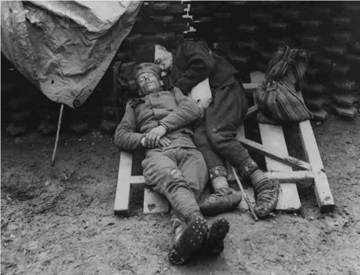 A Serbian soldier rests in a trench, alongside him is his father who came to visit, 1915.