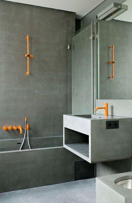 Bright orange bathroom faucets from Vola, designed by Arne Jacobsen, enliven a modernist bath with concrete walls and fixtures.