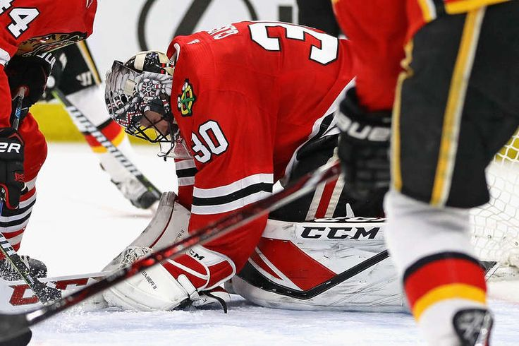CHICAGO, IL - FEBRUARY 06: Jeff Glass #30 of the Chicago Blackhawks covers the puck on a save against the Calgary Flames at the United Center on February 6 2018 in Chicago, Illinois. (Photo by Jonathan Daniel/Getty Images)