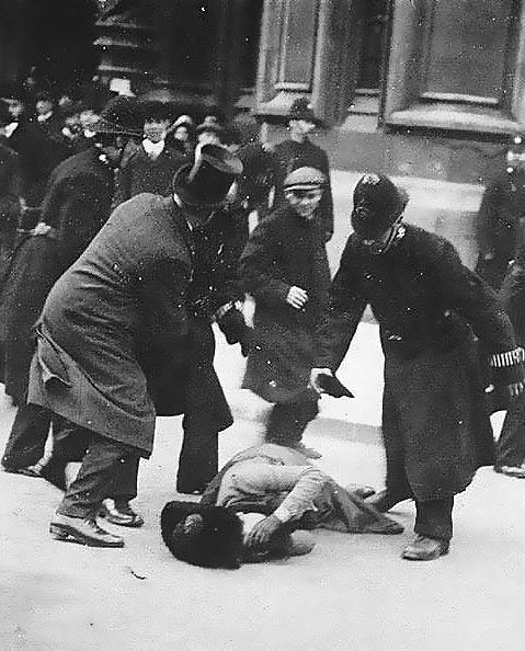 British suffragette Ada Wright as she appeared on the cover of The Daily Mirror on Saturday, November  19, 1910.  In the photograph, she protects her face after having been knocked to the ground several times by the police. The plain-clothed man in the picture is trying to shield her from further violence.