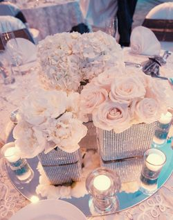 Cluster look of white roses, white hydrangeas, with vases wrapped in bling.