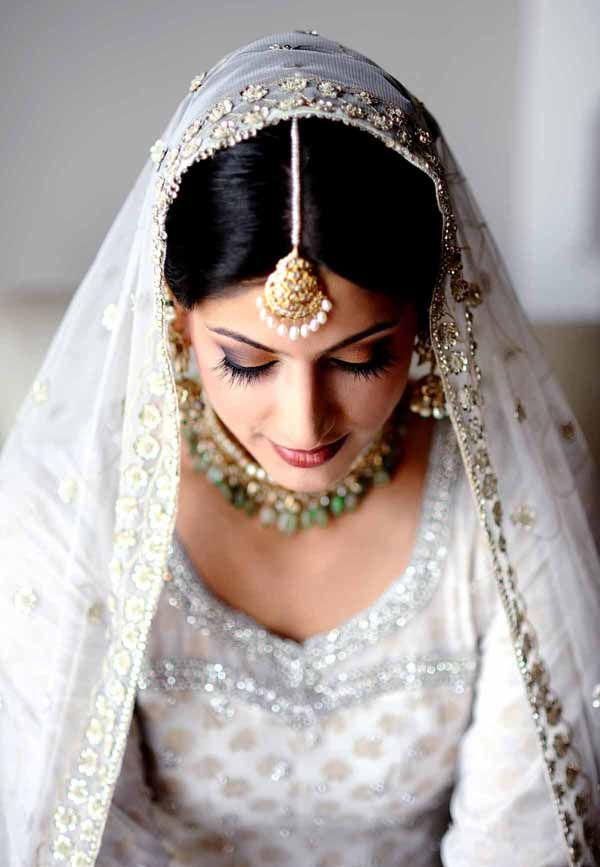 Today's inspiration: This Indian bride looks absolutely beautiful! She is wearing a traditional white lengha that has gold and silver embellishments and brings out her warm makeup. She also has a fabulous pearl tikka, pearl dangling earrings, and a bold necklace. Love the way the chunni is worn.