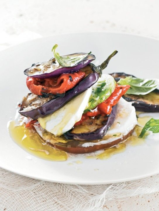 Eggplant and bell peppers summer vegetable stack with mozzarella and tomato slices between the slices of vegetables. Grizzled with olive oil and garnished with basil leaves