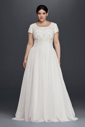Ethereal tulle elegantly flows out from the attached sash waist band of this modest, but stunning plus size wedding dress with short sleeves. Allover beading adorns the scoop neck bodice.  David's Bridal Collection Plus size