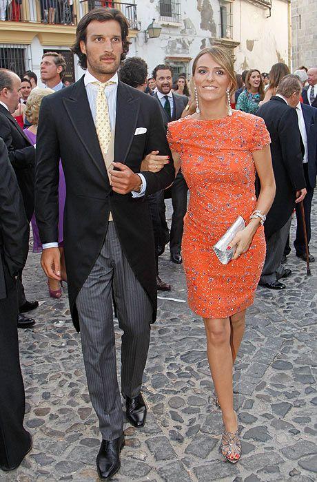 Laura Vecino, en la boda de Mercedes Bohorquez Domecq y Bruno Oliver Bulto, con un vestido cóctel en color naranja y complementos color plata.