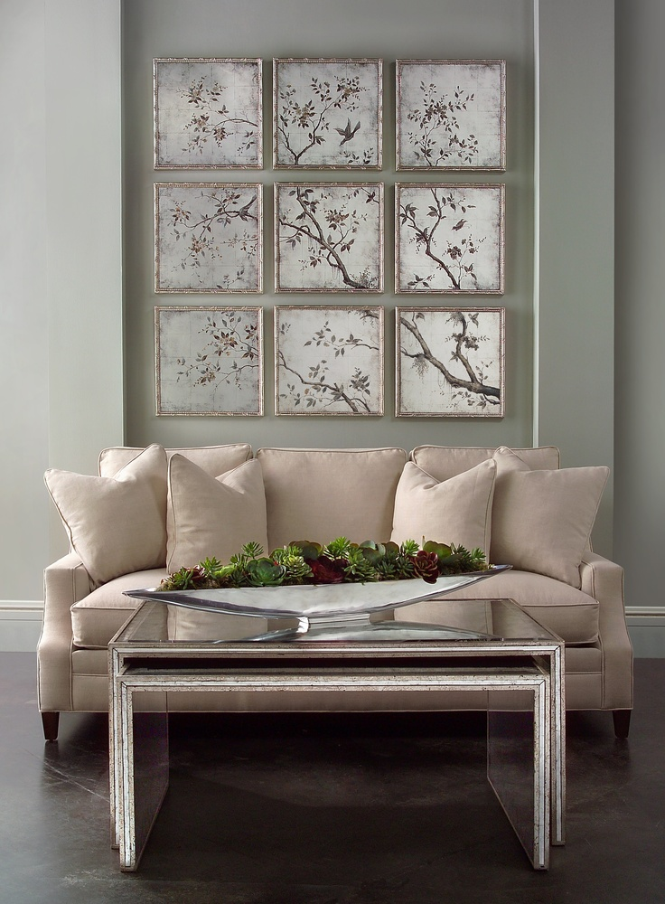 """It's a winter wonderland in the John-Richard High Point showroom. The Juno foxed mirror 4 door credenza sparkles under """"Frost Tree"""" by artist Teng Fei.  Everything that glitters is gold with the incredible wall sconces and lamp. A pair of Chateau arm chairs with deeply scrolling bases flank the cool vignette."""