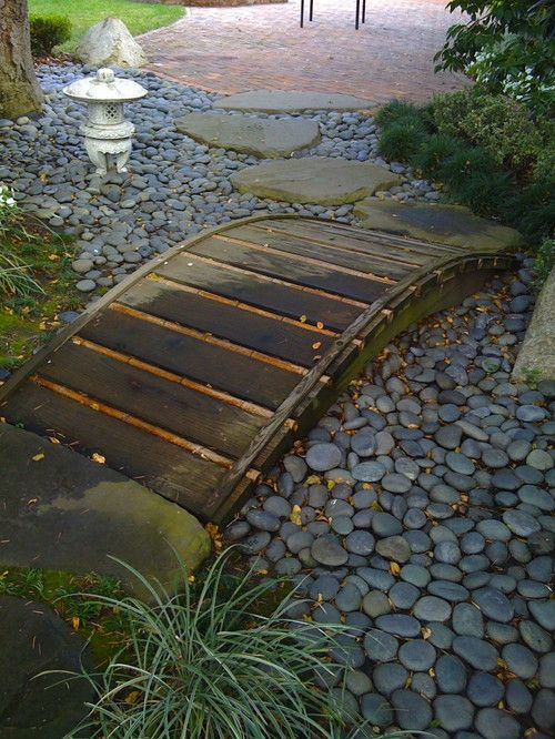 Small wooden bridge over a dry river bed.