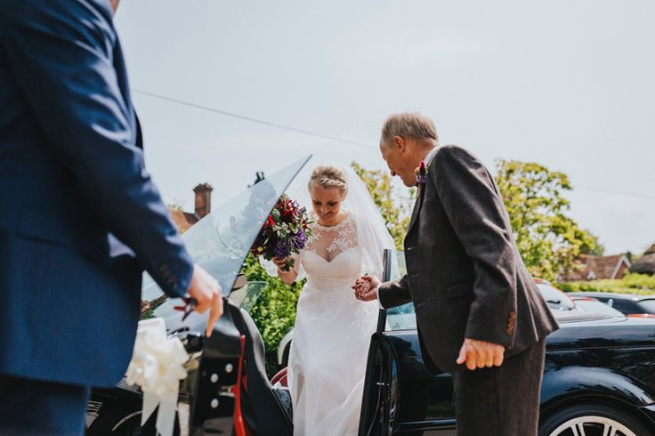 The beautiful bride arrives at the church. How lovely is that lace neckline? Photo by Benjamin Stuart Photography #weddingphotography #bride #weddingdress #herecomesthebride #weddingday