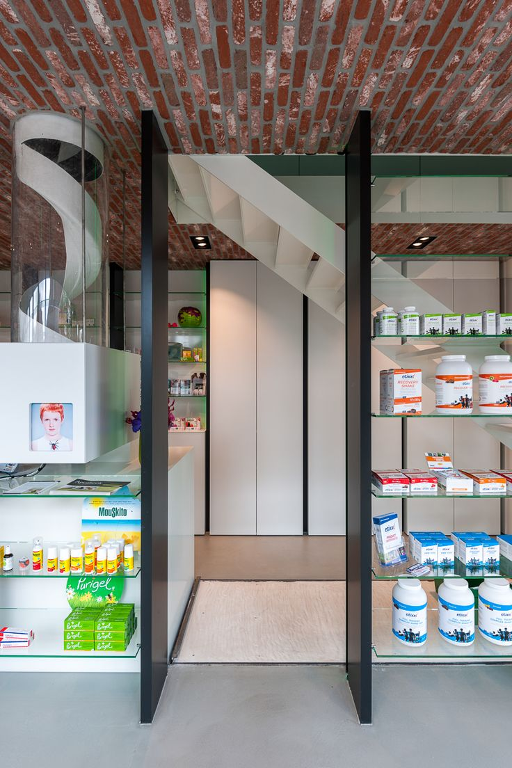 Automatic Distributionsysteem of presripted medication, steel columns, brick ceiling, steel stairs | Pharmacy in Berendrecht (Belgium) by sculp[IT]architects | brick ceiling and steel colums which are also the windowprofiles ànd supporting for the glass shelves | photograpy www.roymans.com