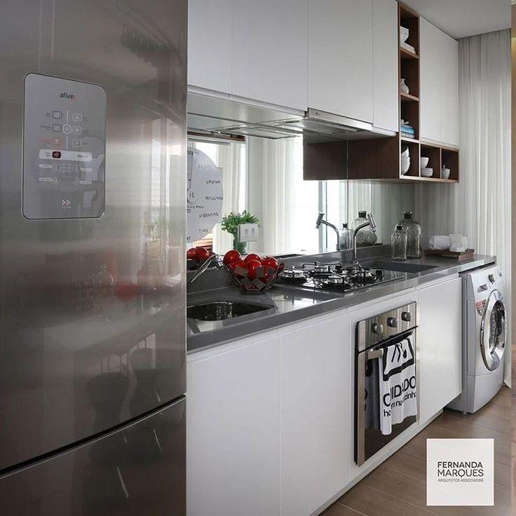 Cozinha toda branca com pequeno detalhe em madeira e bancada em silestone cinza . Área de serviço integrada. Trocar eletros para brancos.