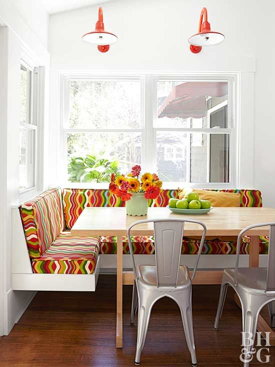 Don't waste precious corner space. Instead, fit a cute and functional banquette into the area. This space affords a view of the outdoors and is filled with natural light thanks to big windows surrounding the banquette. The neutral colors, carried over from the adjoining kitchen, are punched up with green, pink, and red seat cushions.