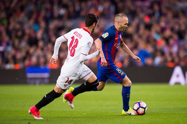 Andres Iniesta of FC Barcelona conducts the ball past Sergio Escudero of Sevilla FC during the La Liga match between FC Barcelona and Sevilla FC at Camp Nou stadium on April 5, 2017 in Barcelona, Catalonia.