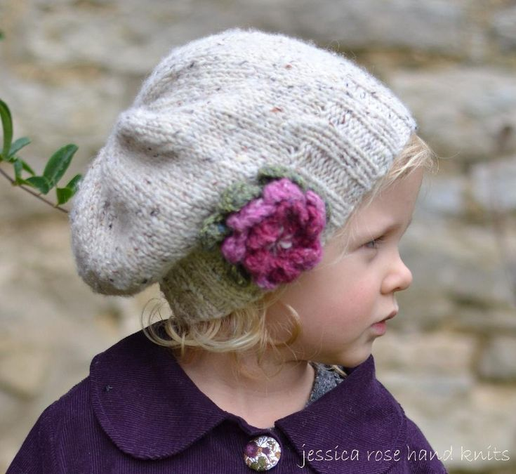 A pretty tweedy girls Aran hat with a knitted flower that is simple and quick to knit - find the pattern on LoveKnitting!