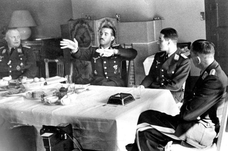 Während des Geburtstagsempfangs im April 1941 bei Generalleutnant Theodor Osterkamp (r.) schildert der Jagdflieger der deutschen Luftwaffe, Oberstleutnant Adolf Galland (2.v.l.) einen Luftkampf; 2.v.r. Oberstleutnant Werner Mölders. (Dreesen) 10443-41 - Galland at Osterkamp's 49th birthday describing a combat, April 1941.