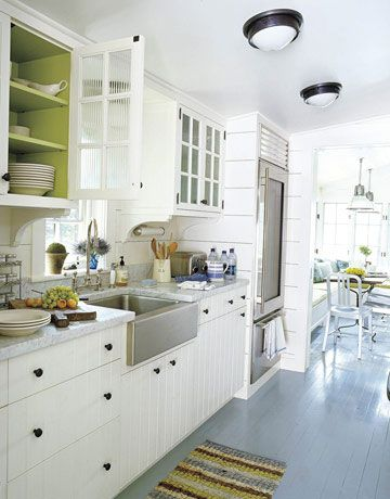 This simple 1939 lakeside cottage marries modern and traditional, and its kitchen, designed by Gil Schafer, follows suit. The floor is painted in Pratt & Lambert's Gunnel. Ceiling lights are from Urban Archaeology, cabinet hardware from Sun Valley Bronze. Elkay stainless-steel Farmhouse sink, Barber Wilsons polished nickel faucet, Sub-Zero refrigerator.