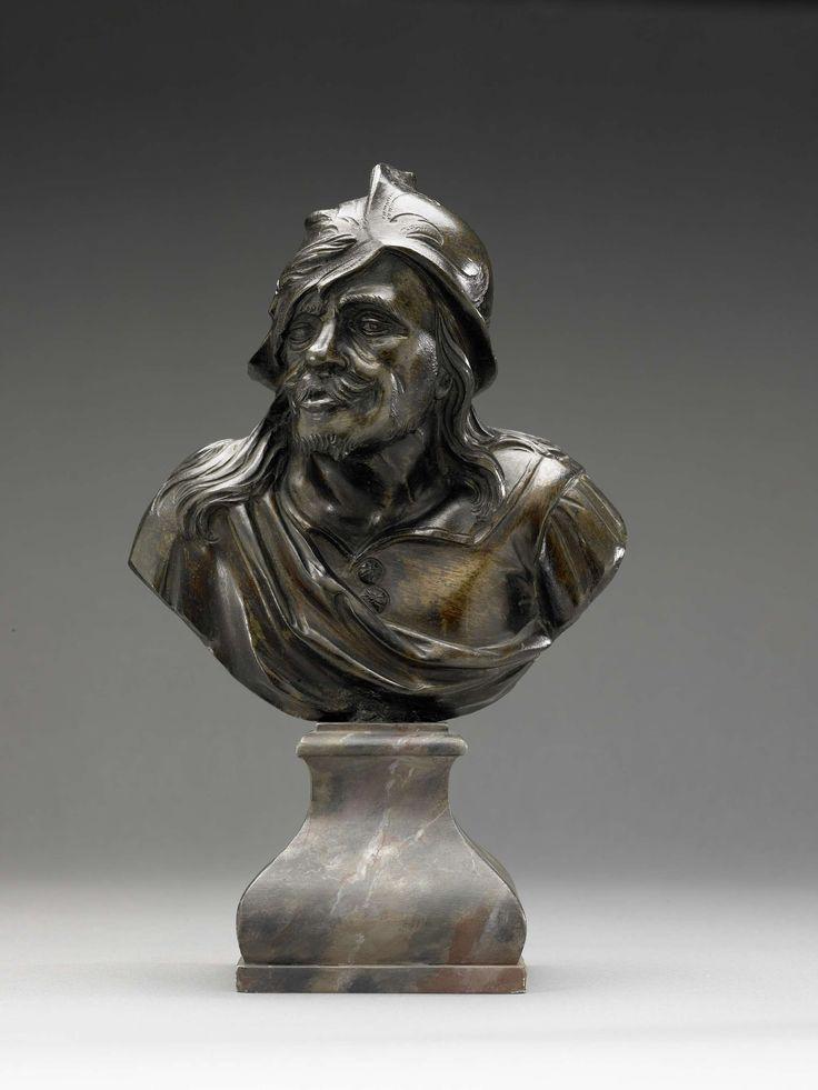 anoniem | Borstbeeld van man, attributed to Pieter Xaveri, c. 1675 | De even naar links gewende kop met cynische gelaatsuitdrukking vertoont zware plooien, borstelige wenkbrauwen, een knevel en een stoppelig baardje; de haren vallen losjes over de schouders. Hij draagt een helmvormig hoofddeksel, waarop een ondefiniëerbaar voorwerp (een pluk haar of een tabaksblad?) is gehecht; door een split komt een haarlok tevoorschijn. Hij draagt een wambuis met knopen, waarvan de kraag is opengeslagen…