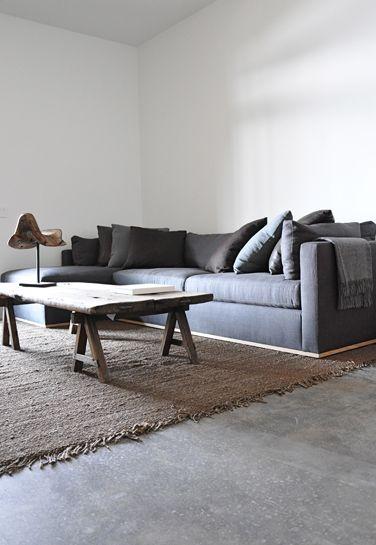 Un salon au look résolument moderne grâce à l'utilisation du béton ciré et de mobilier en bois brute. Une tendance très forte aujourd'hui en décoration