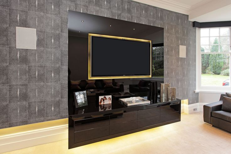 This wall-hung cabinet and television surround were clad in black glass. The doors are on push-to-open catches and the cabinet contains audio-visual equipment by Andrew Manning Furniture