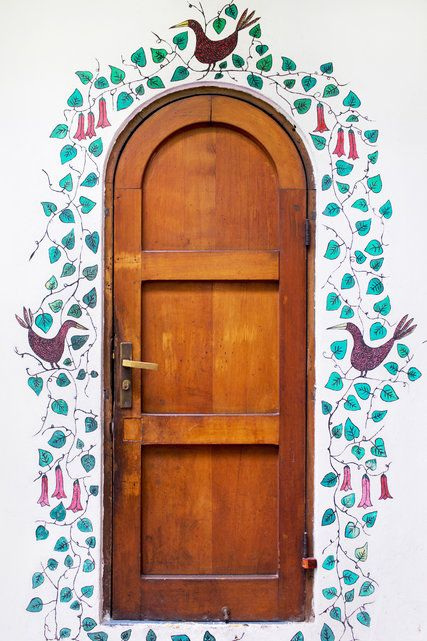 Birds and vines wind around the arched door of La Chascona, Pablo Neruda's home in Santiago, Chile. Credit Danielle Villasana