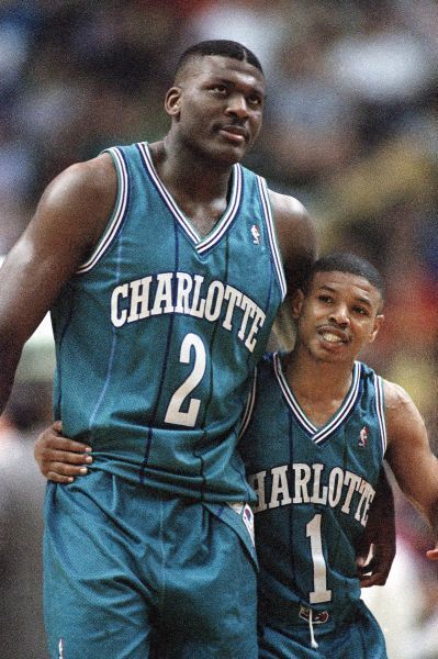 Larry Johnson (left) hugs Charlotte Hornets teammate Muggsy Bogues during the final seconds of an overtime win in 1993.