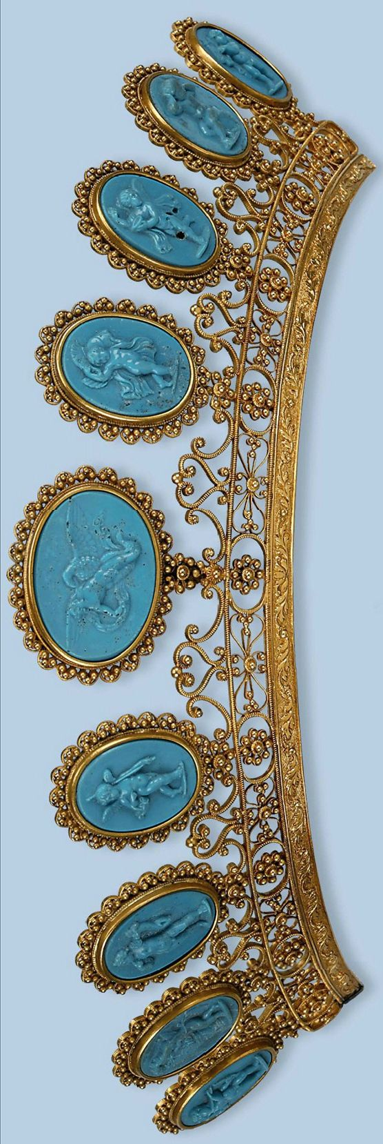 A parure comprising a tiara with two mounts, a pair of bracelets, a necklace, and a pair of earrings, each composed of a row of blue pressed glass cameos in various sizes, depicting philosophers, classical gods, and various scenes after the antiques, within borders of cannetille work and filigree mounts, French, circa 1800, w/fitted case.