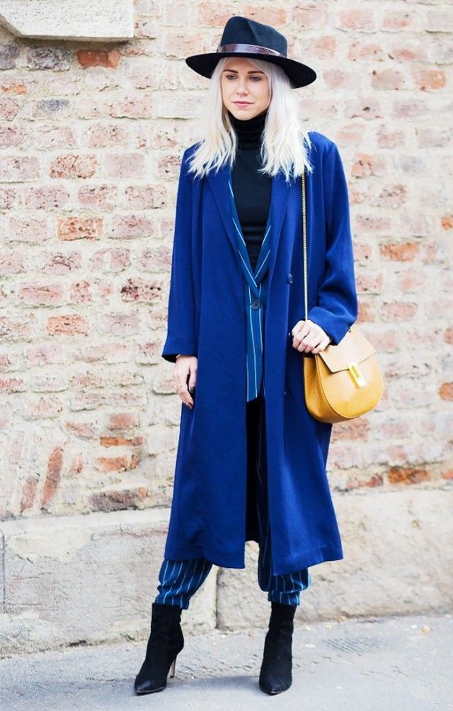 A royal blue overcoat is layered over a blue striped suit and a black turtleneck. The look is completed with black suede booties, a black wide-brim hat and a Chloé Drew Bag.